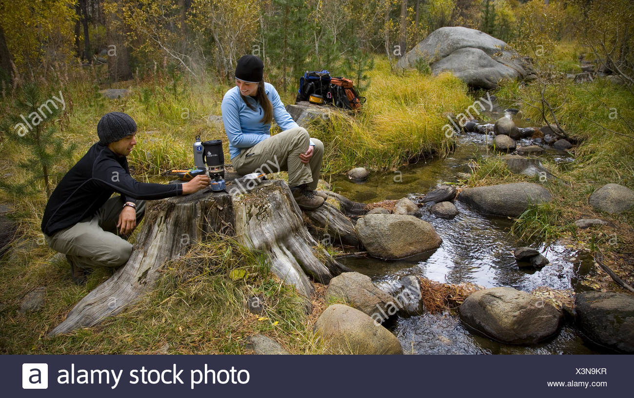 Backpackers cook lunch near a stream. - Stock Image