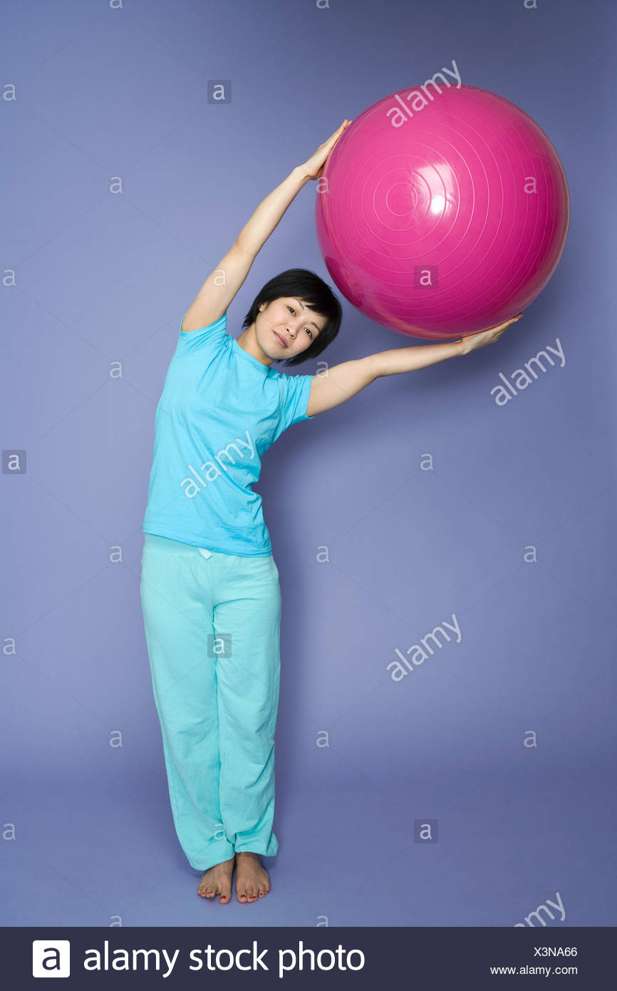 A woman standing and holding a fitness ball - Stock Image