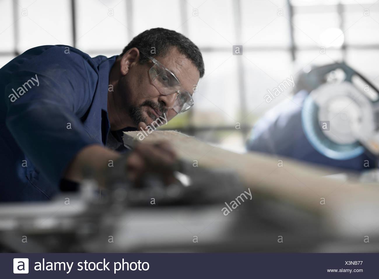 Carpenter checking straightness of plank in workshop Stock Photo