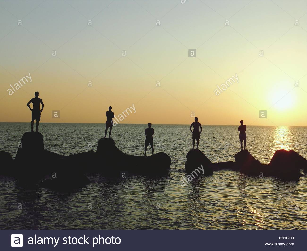 Group Of Men Standing On Breakwaters - Stock Image