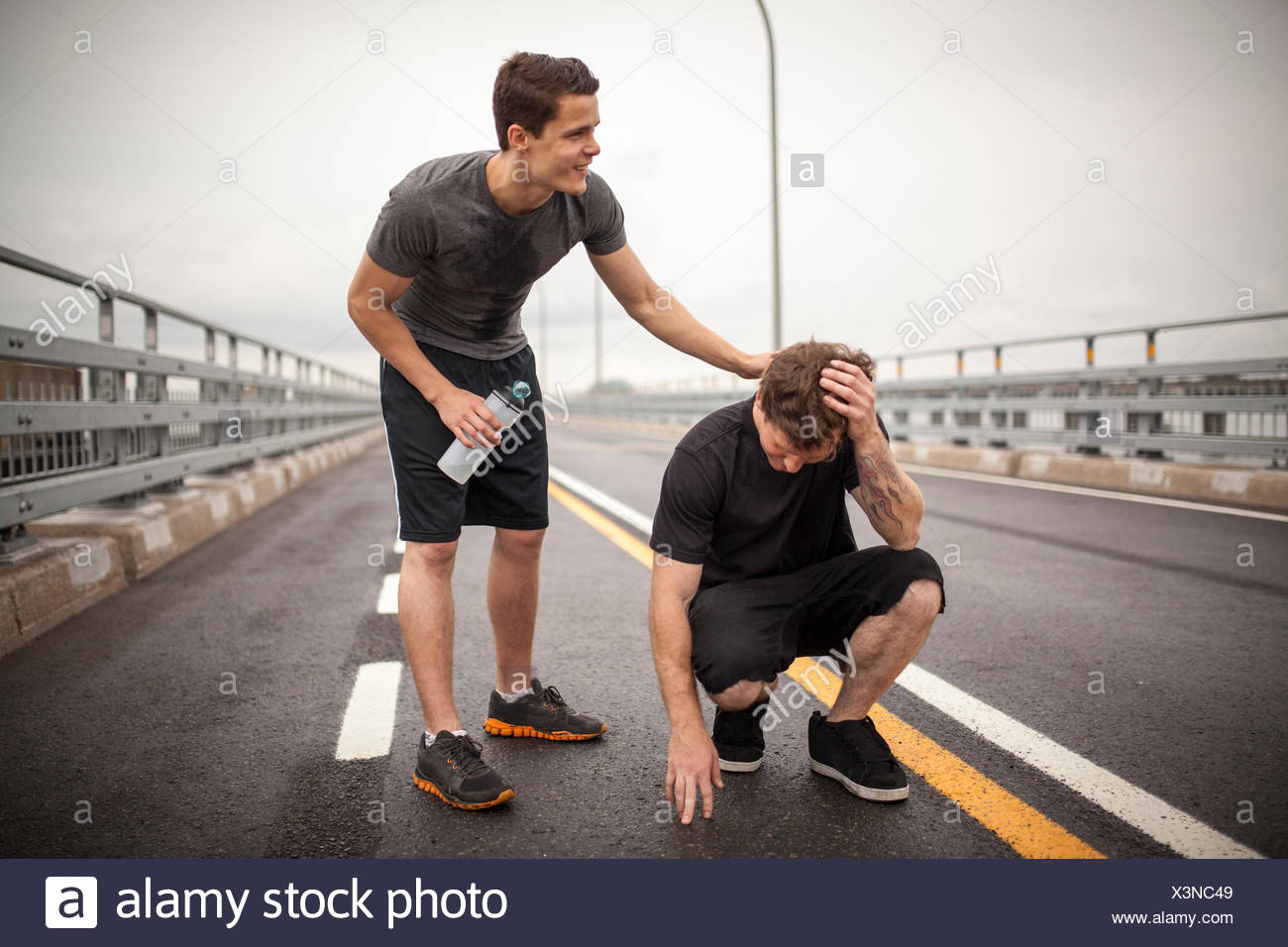 Young man reassuring friend - Stock Image