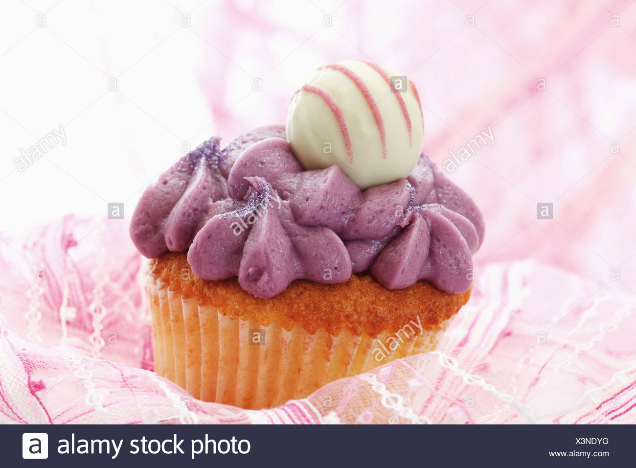 Close up of buttercream black currant cupcake with chocolate truffle Stock Photo