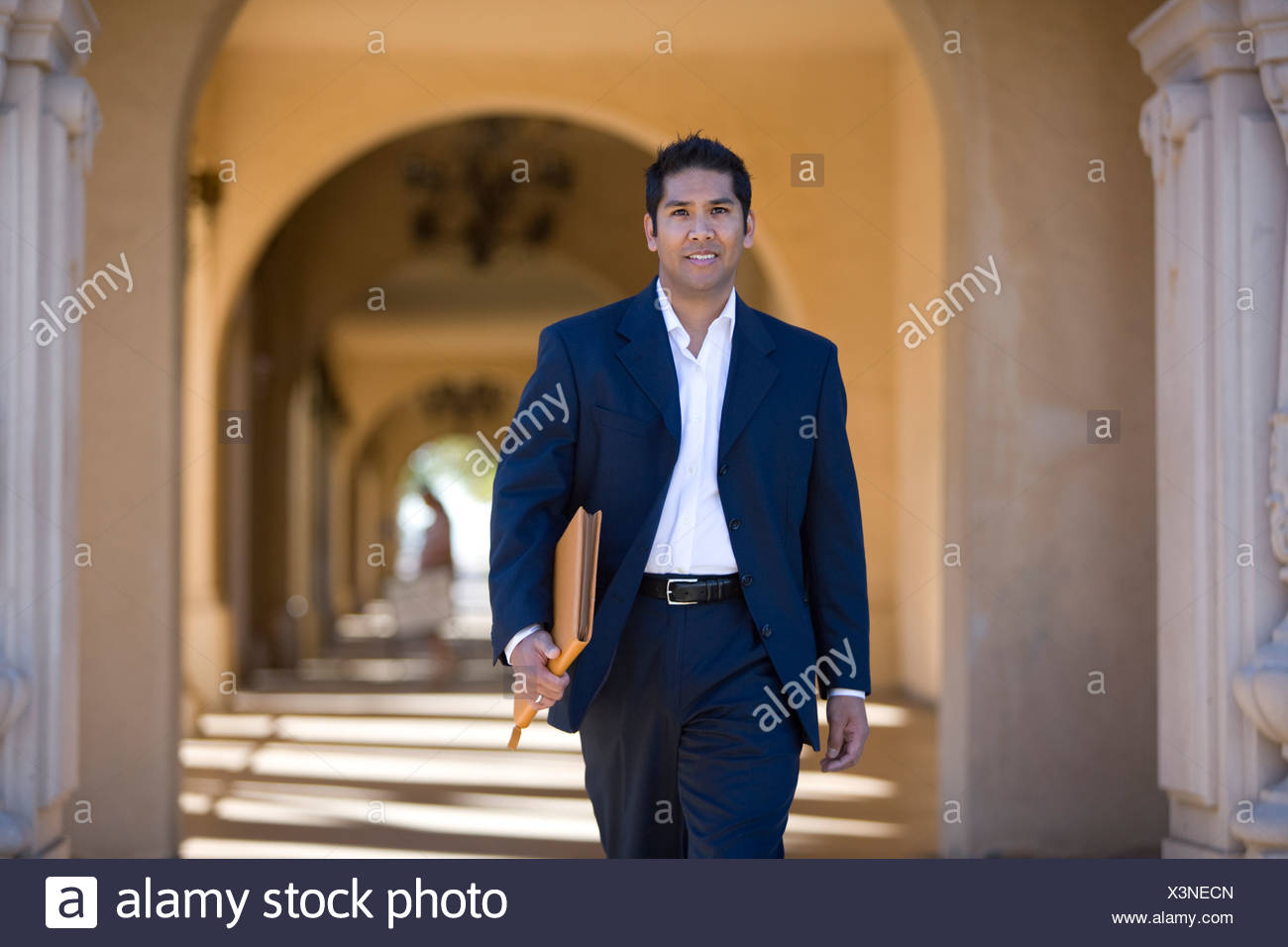 Businessman walking through archway - Stock Image