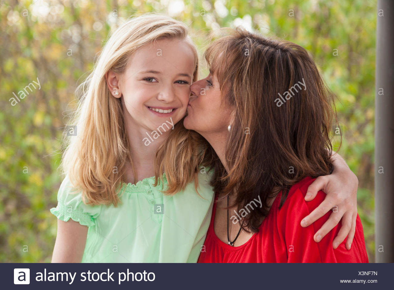 Woman kissing her daughter, Bavaria, Germany - Stock Image