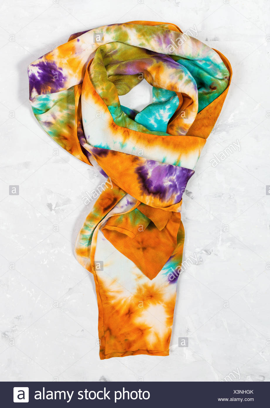 tied hand painted silk scarf on concrete plate - Stock Image