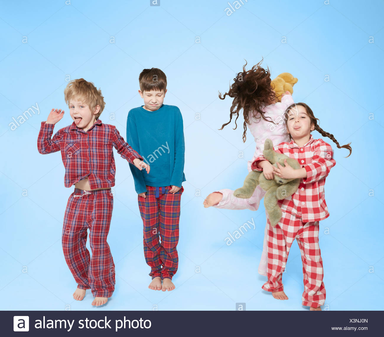 Children in pyjamas dancing and jumping - Stock Image