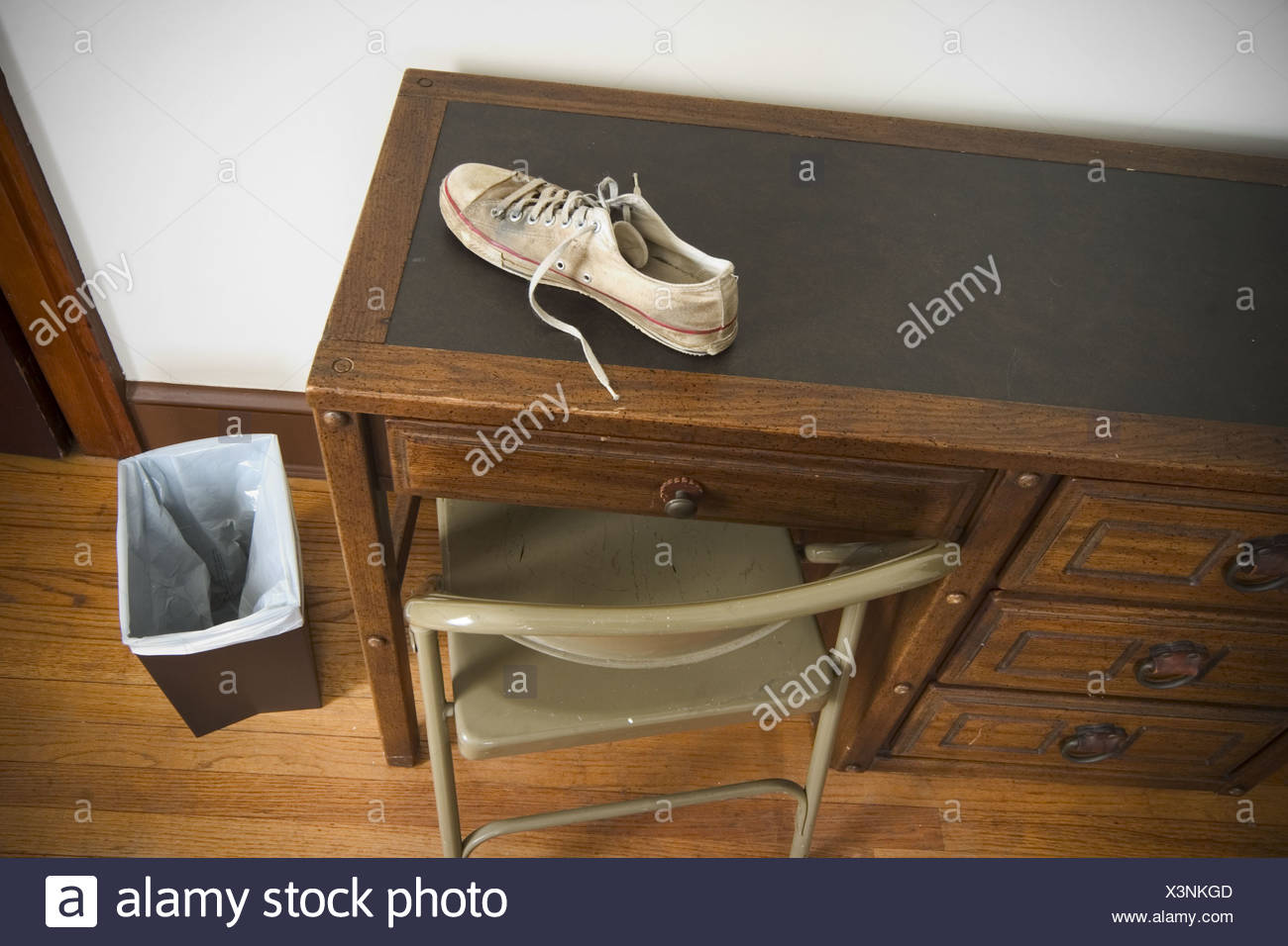 Man´s sneaker on top of a desk in a bedroom. - Stock Image