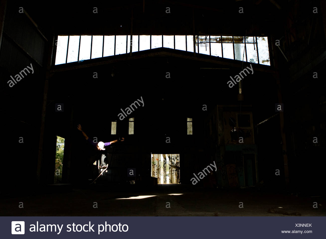 A skater ollies in an abandoned warehouse on the Central Coast, New South Wales, Australia. - Stock Image