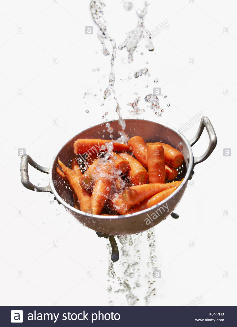 Water falling through colander with fresh carrots - Stock Image