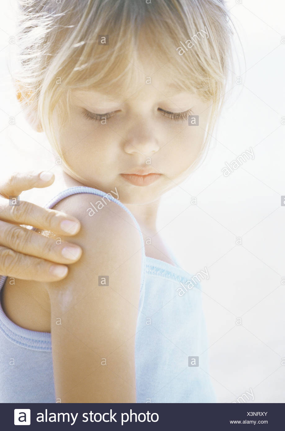 Girl having sunscreen applied to shoulder - Stock Image