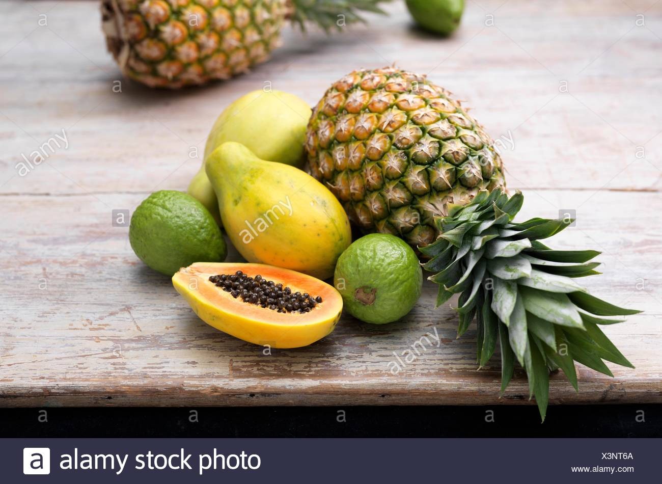 Fruit ingredients for tropical juice on wooden table - Stock Image