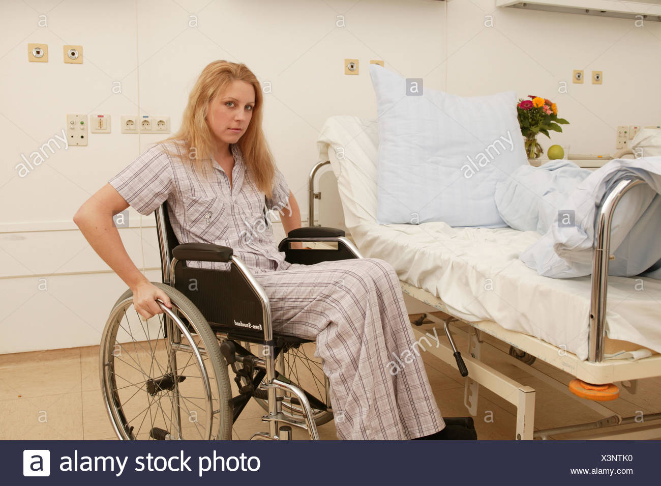 Wards, patient, invalid, wheel chair, sit, suffer sadly, medicine, hospital, clinic, hospital, sickbed, bed, disease, hospitalisation, convalescense, health, woman, young, 20-30 years, invalid, feet, impediment, hemiplegia, destiny, grief, worries, facial play, emotion, ailment, Ti7 - Stock Image