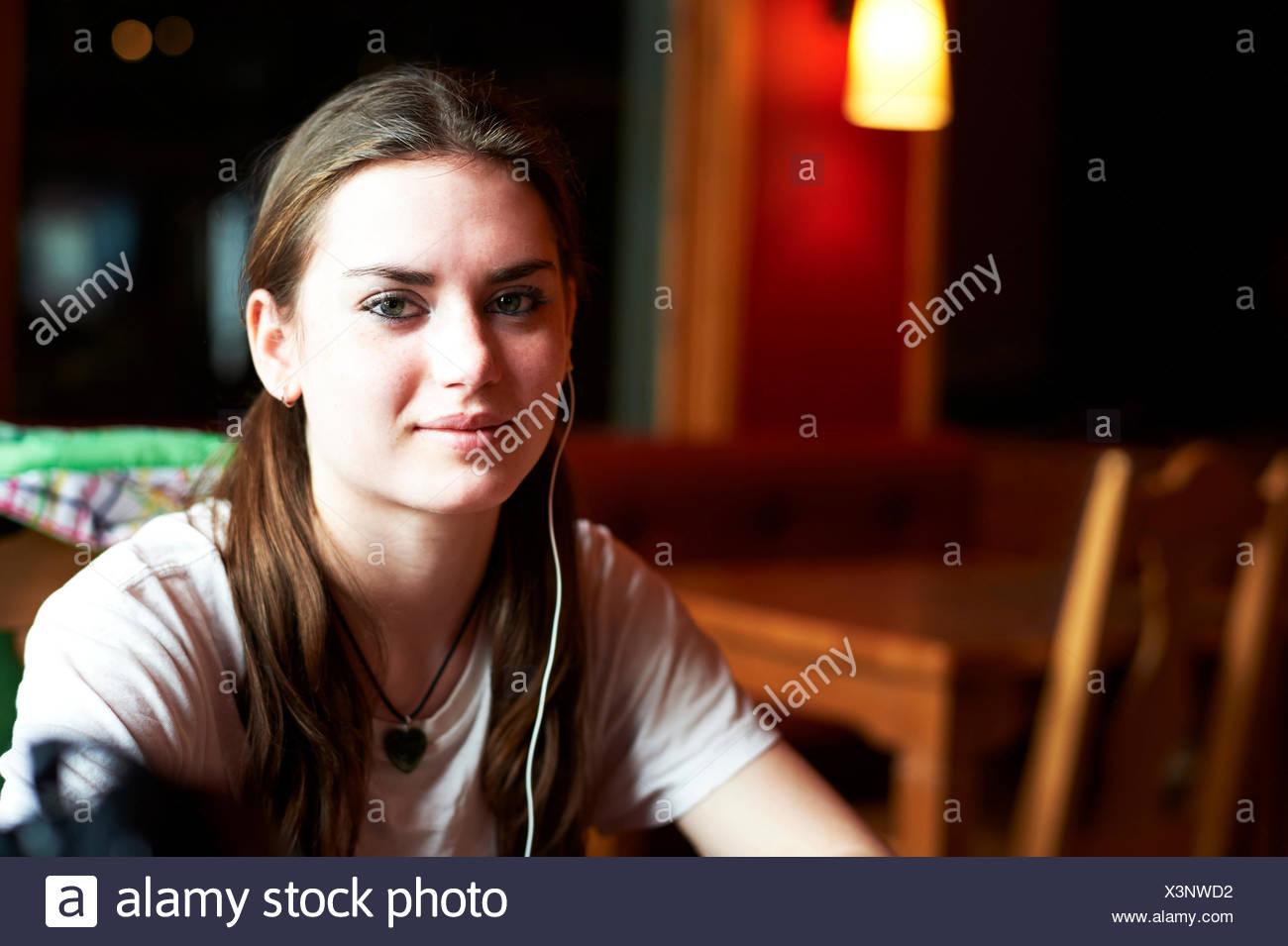 Portrait of teenage girl wearing earphones - Stock Image