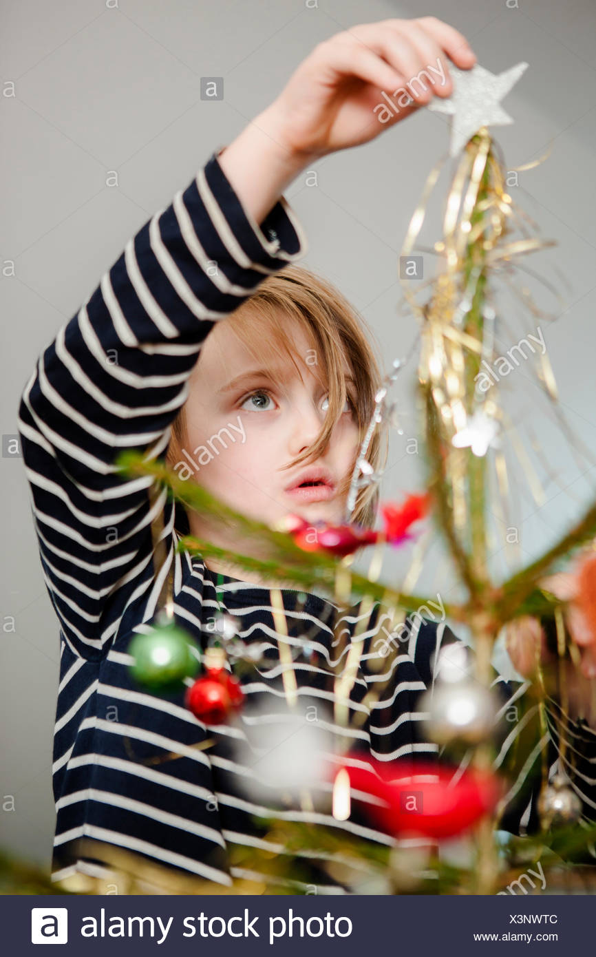 Girl (6-7) decorating Christmas tree - Stock Image