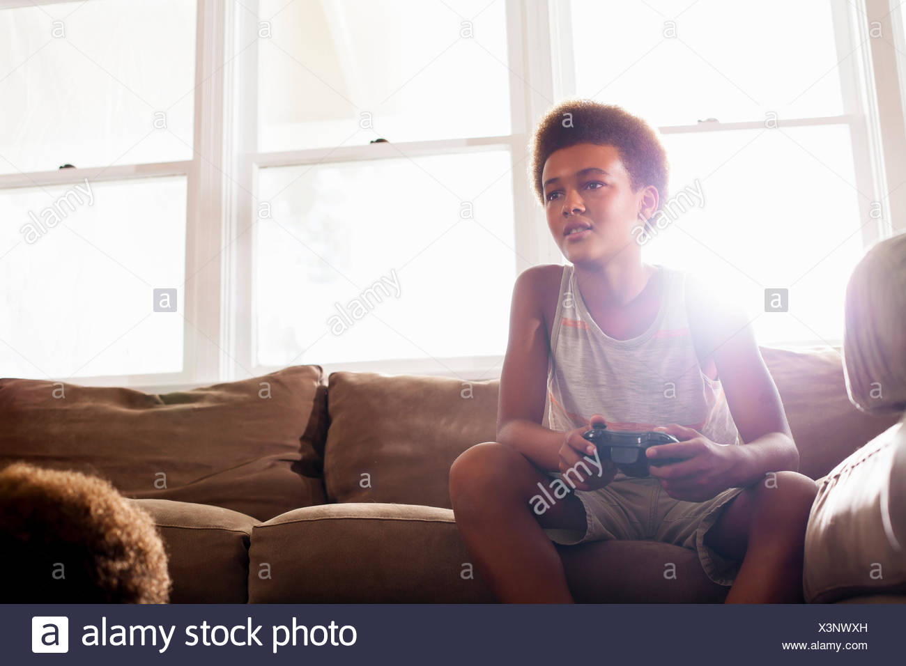 Boy using game controller from living room sofa - Stock Image