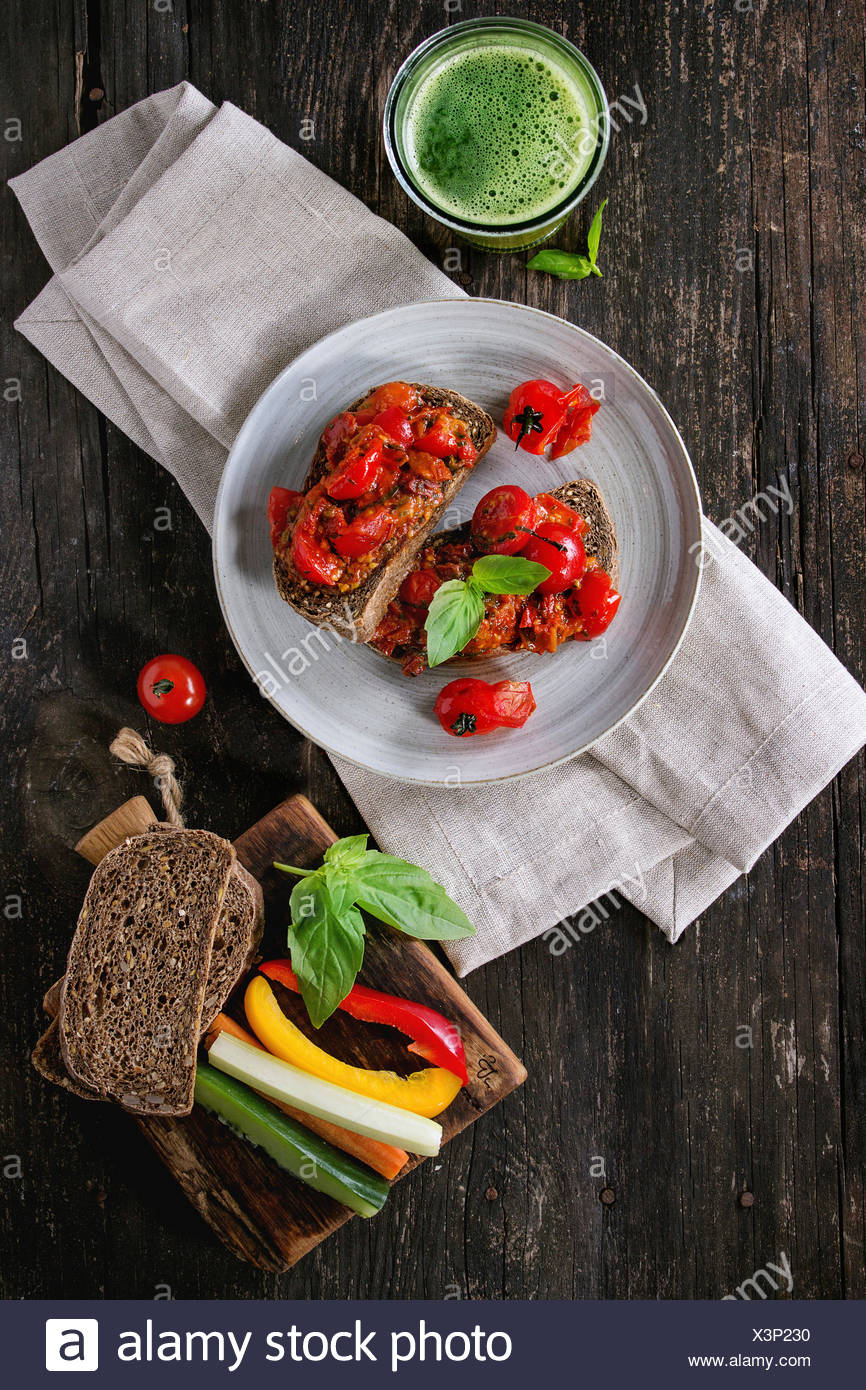 Italian tomato bruschetta with baked cherry tomatoes and sliced vegetables, served on gray ceramic plate with textile napkin and Stock Photo