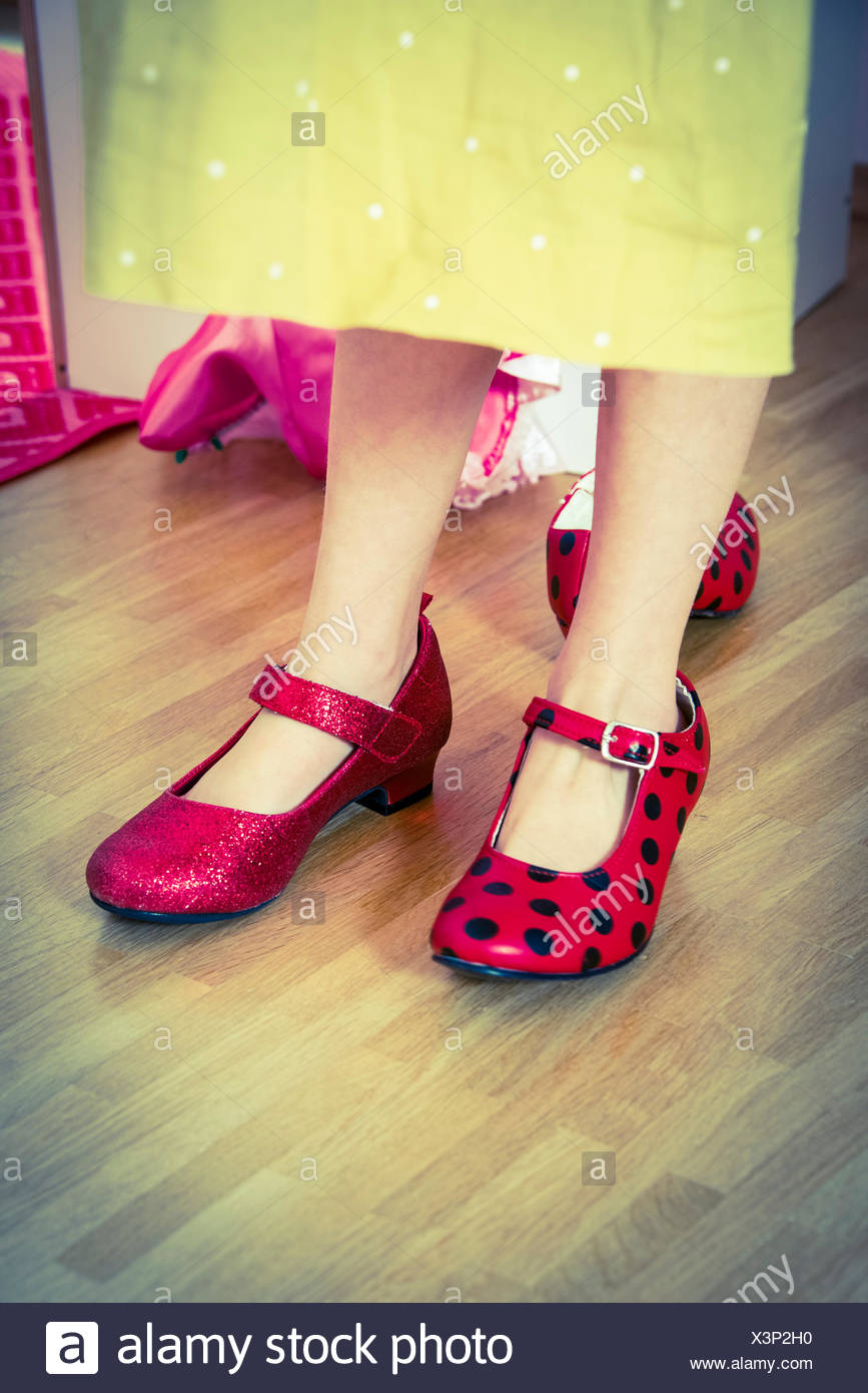 Little girl trying out high heels, close-up - Stock Image