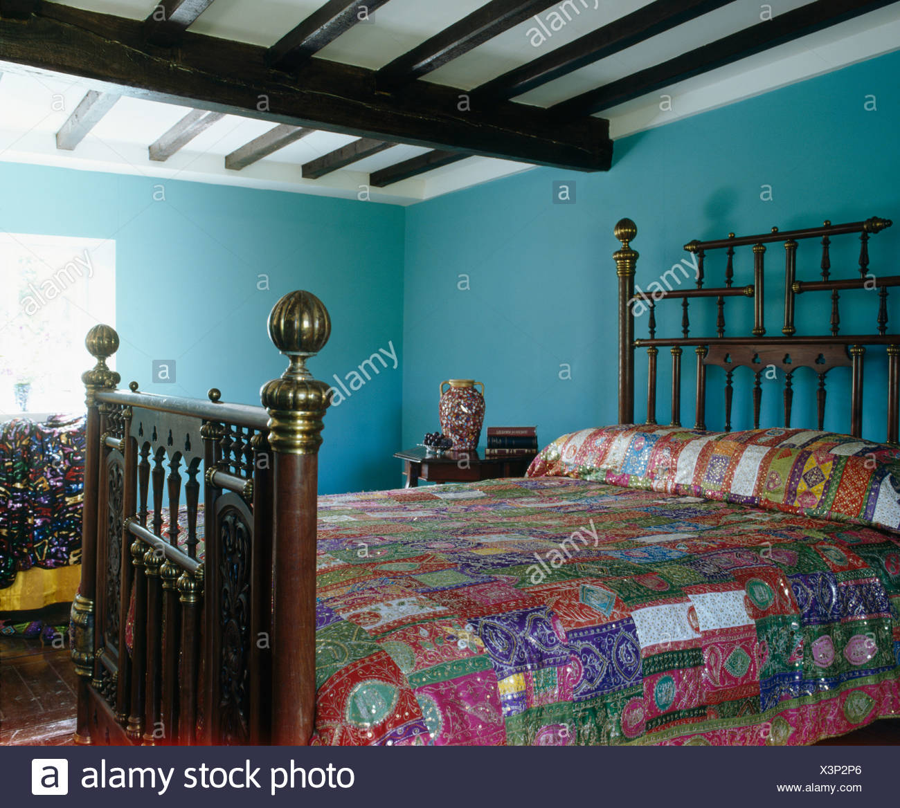 Colorful patchwork quilt on antique carved wooden bed in blue country bedroom with beamed ceiling Stock Photo