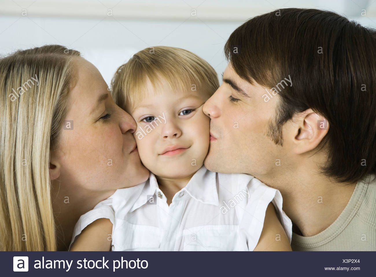 Parents kissing little boy's cheeks, boy looking at camera - Stock Image