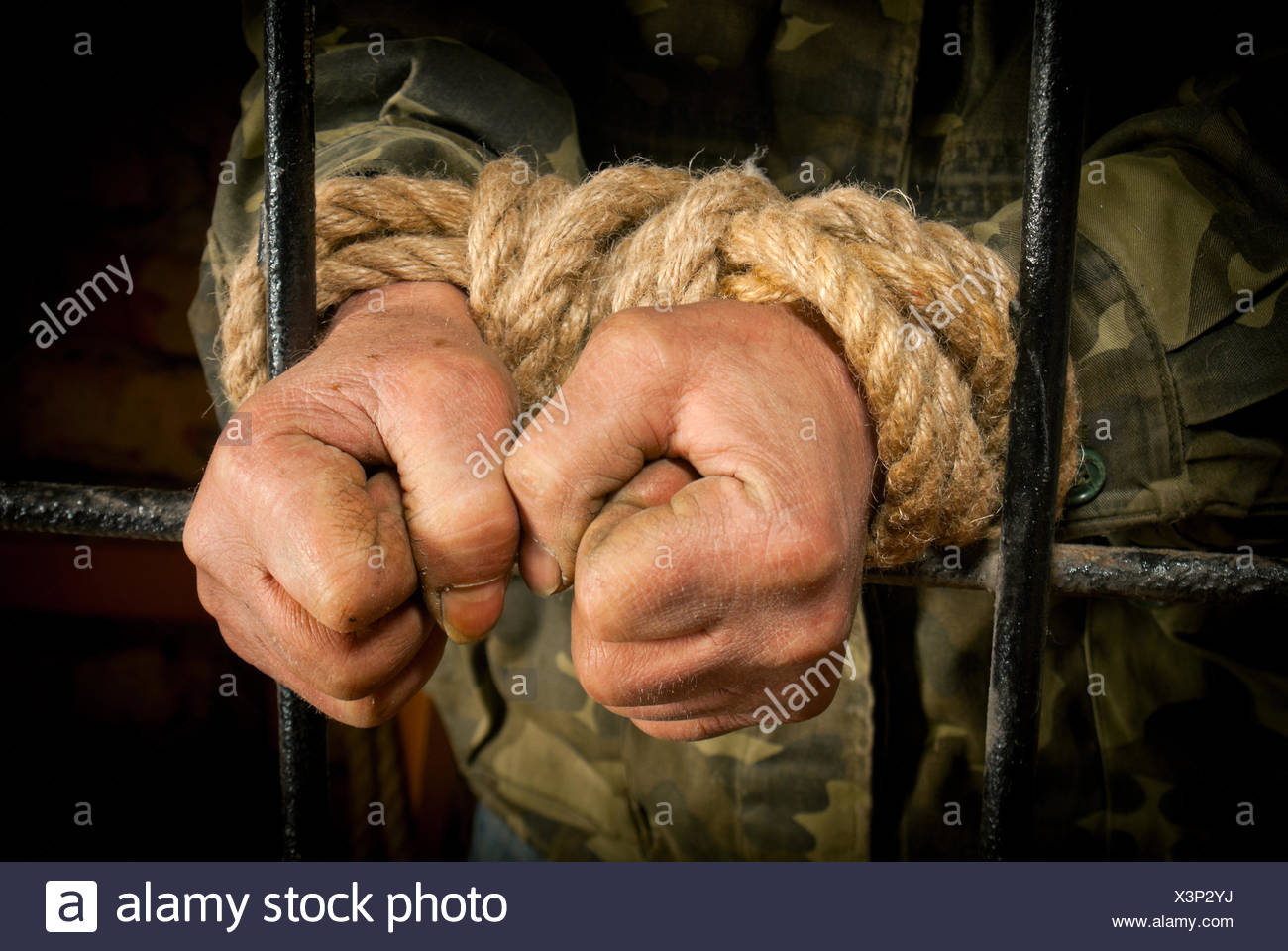 Man with hands tied up with rope behind the bars - Stock Image