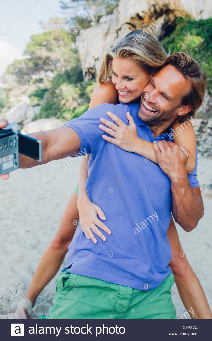 Couple filming themselves with a camcorder at the beach - Stock Image