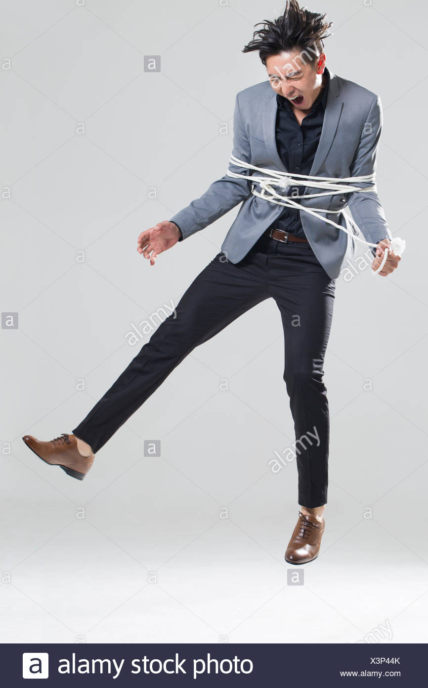 Young man tied up with rope - Stock Image