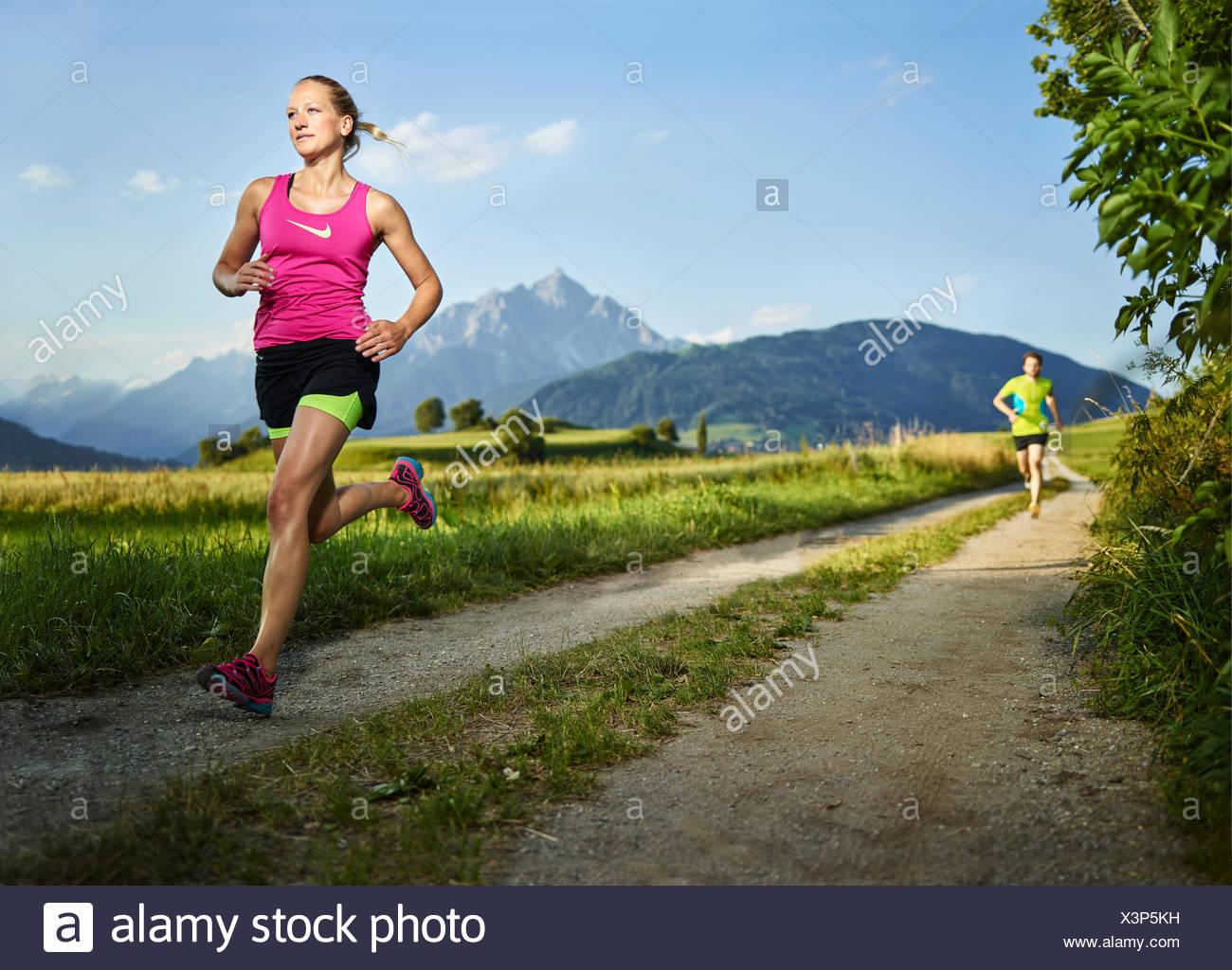 Young woman in her twenties running on path through fields, Rosengarten, Tyrol, Austria - Stock Image