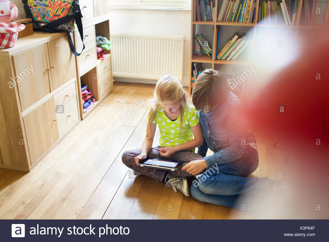 Brother and sister sharing and using digital tablet - Stock Image