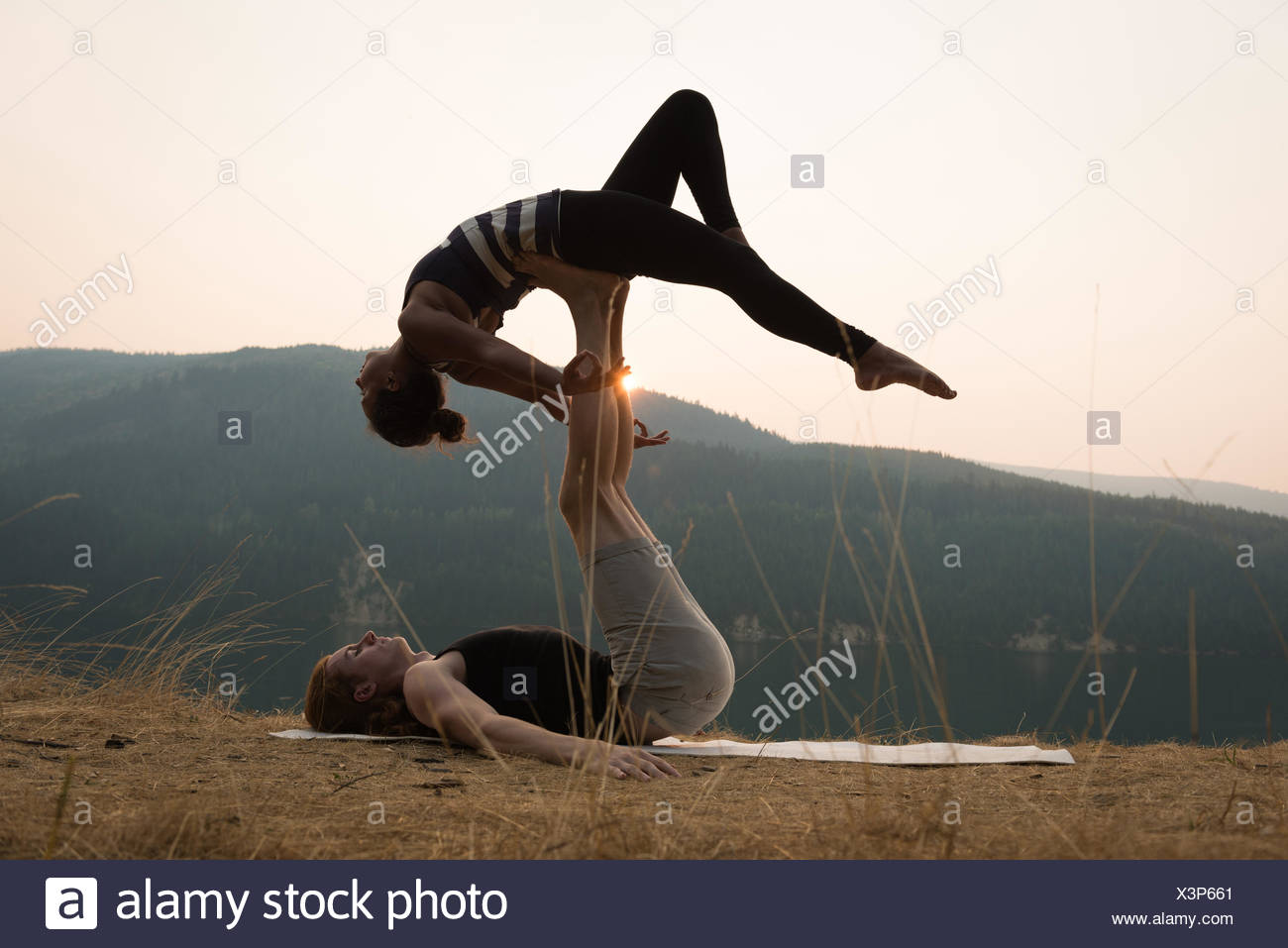 Sporty couple practicing acro yoga in a lush green ground - Stock Image