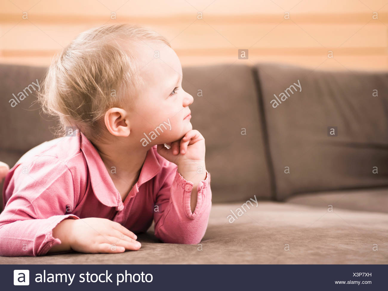 Baby girl lying sofa on thinking side profile - Stock Image
