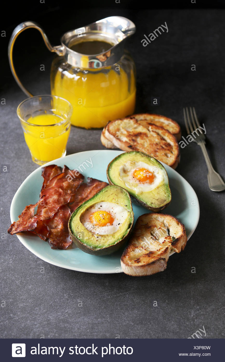 Breakfast with eggs baked in avocado,bacon ,bread toast and orange juice Stock Photo