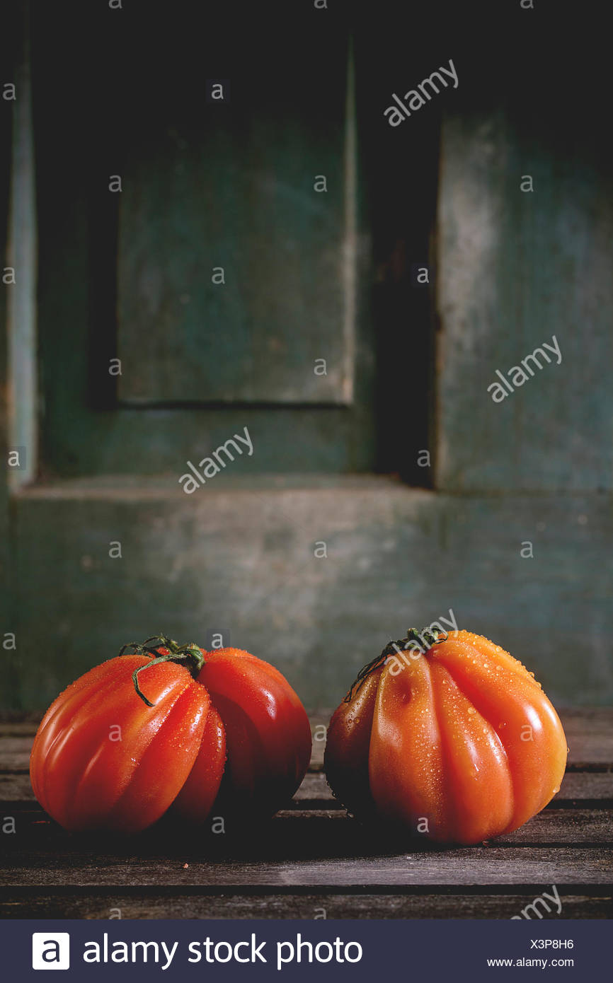 Two big red tomatoes RAF over old wooden table. Dark rustic atmosphere - Stock Image