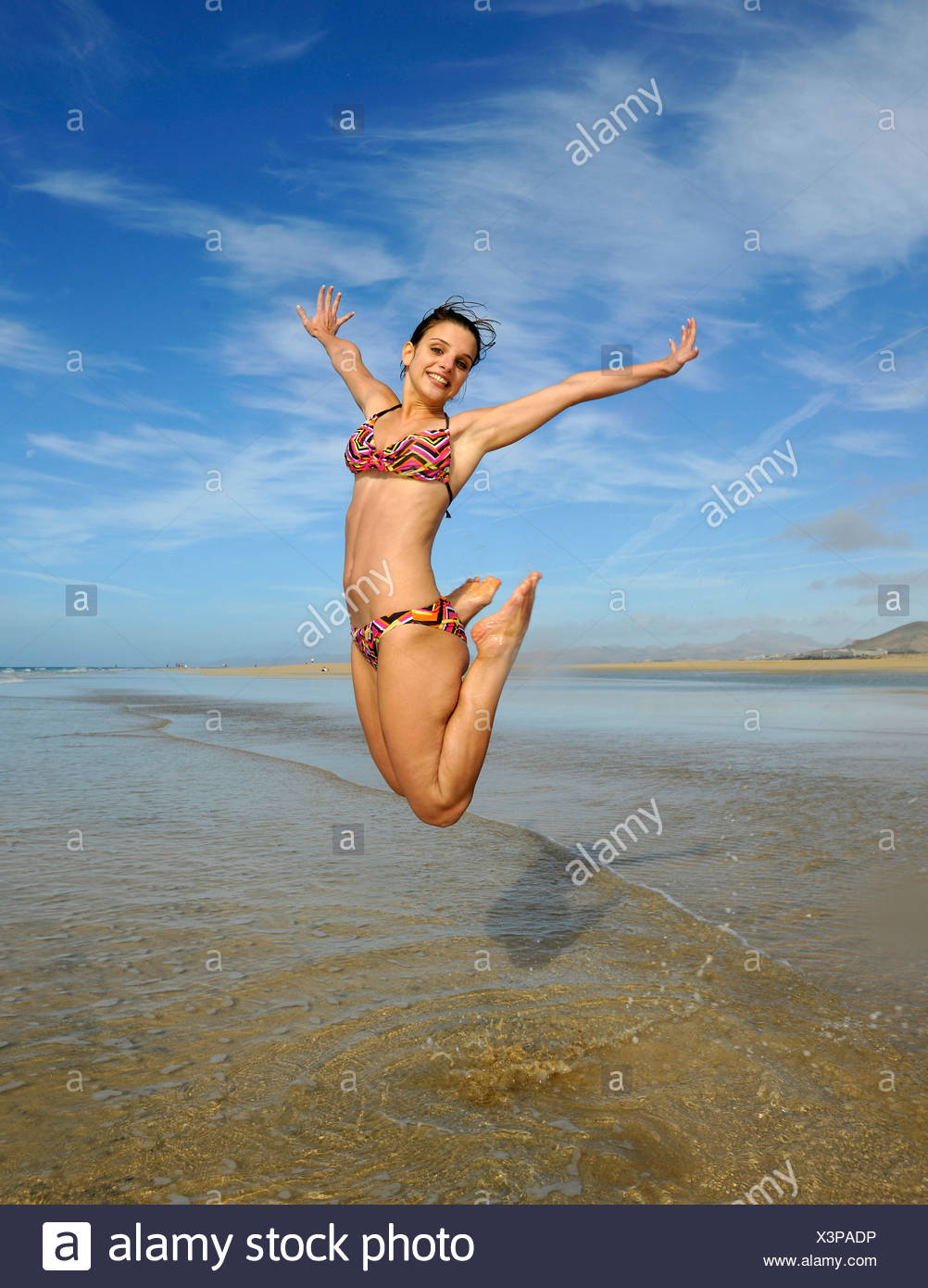 Leap into the air, young woman at the sea, symbolic image for vitality, lust for life, Playa de Sotavento de Jandia beach - Stock Image