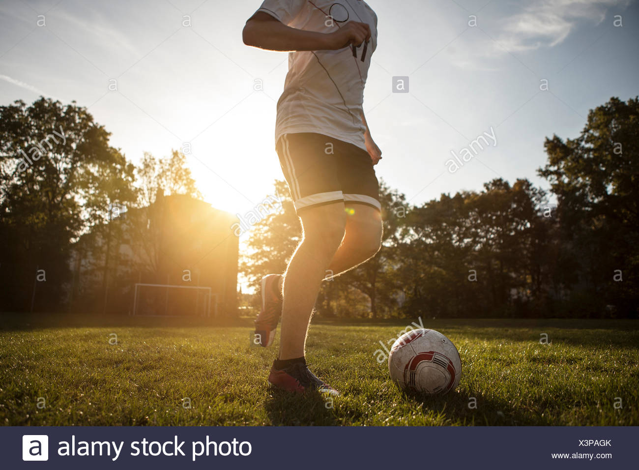 Teenager playing soccer on soccer pitch - Stock Image
