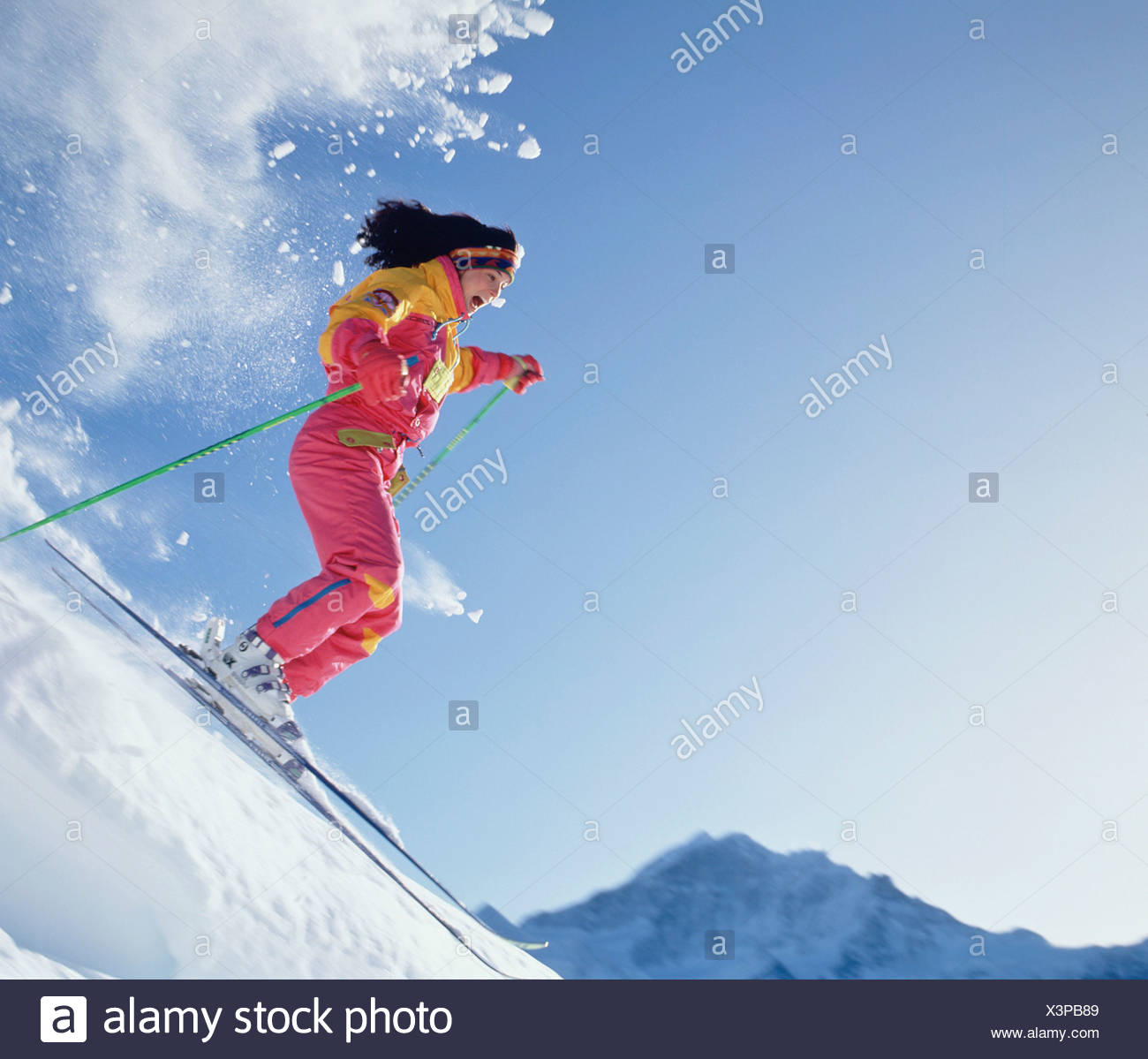 Woman skiing down snow covered mountain slop. Swiss Alps. - Stock Image