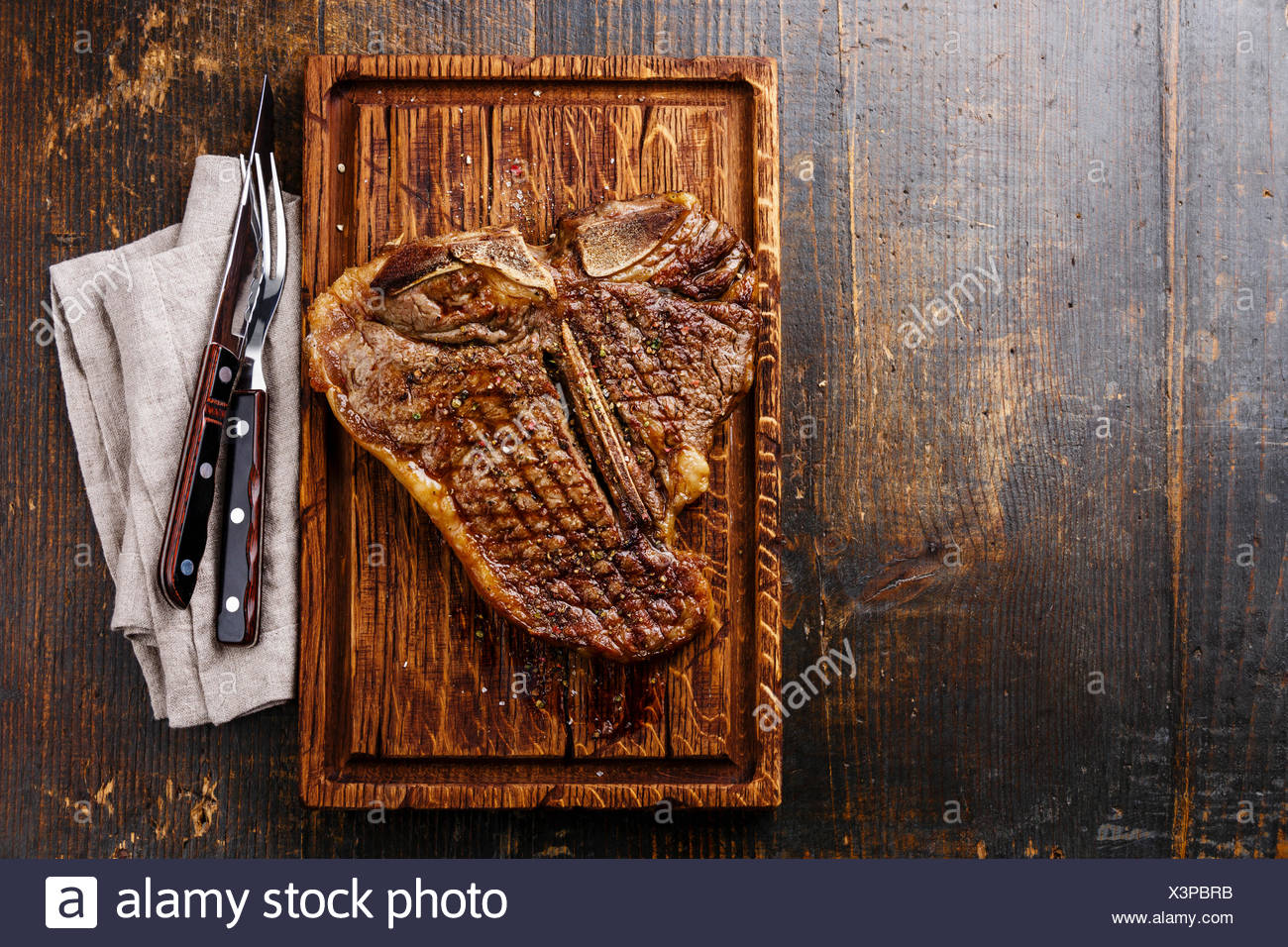 Grilled T-Bone Steak with fork and knife on serving board on wooden background Stock Photo