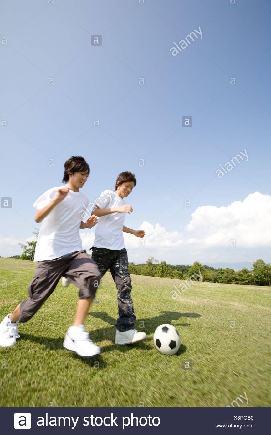 Two teenage boys playing soccer - Stock Image