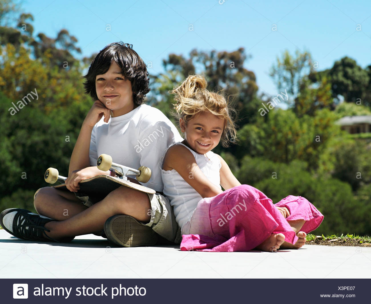 Boy 10 12 and girl 6 8 sitting in park boy with skateboard in lap smiling portrait - Stock Image