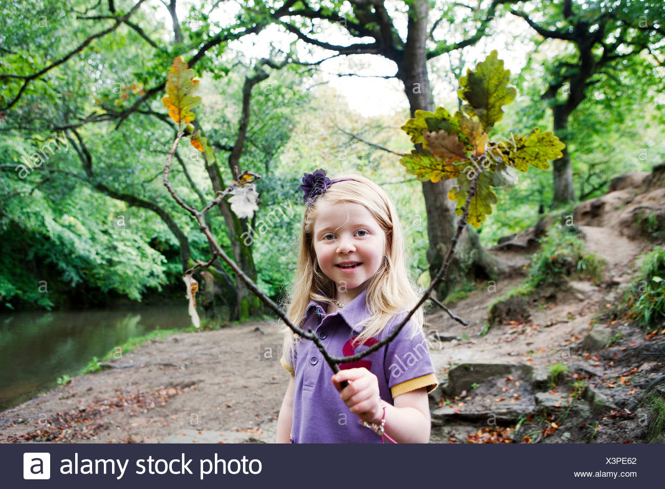 Girl holding an oak branch in a woodland - Stock Image