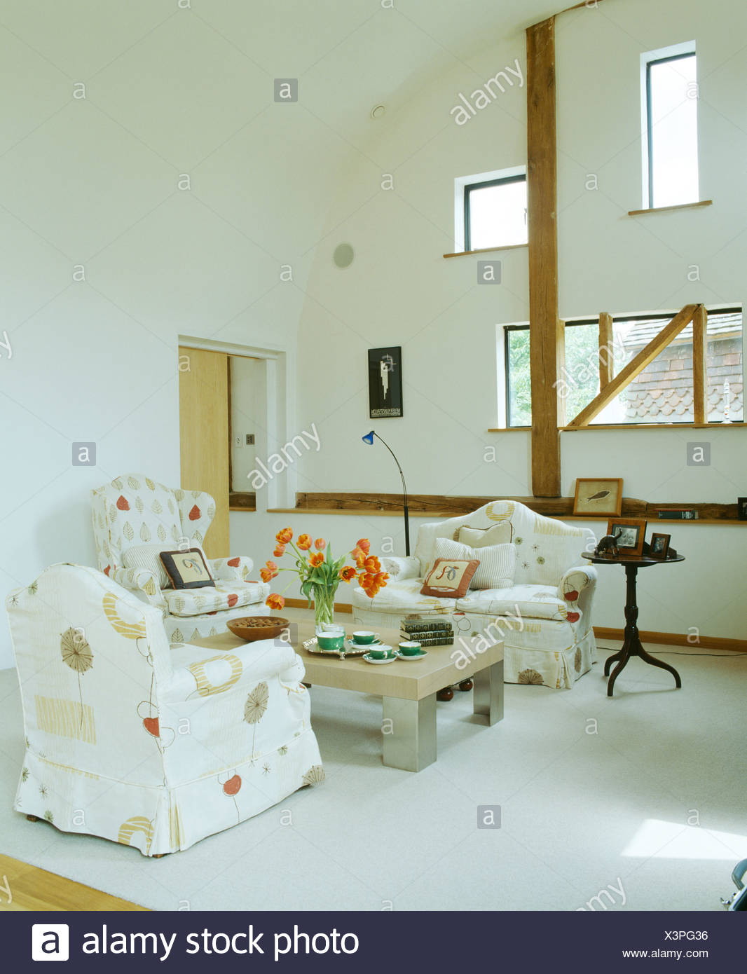 Patterned Armchairs And Sofa In White Double Height Country Living Room  Extension With White Carpet And Low Wood Table