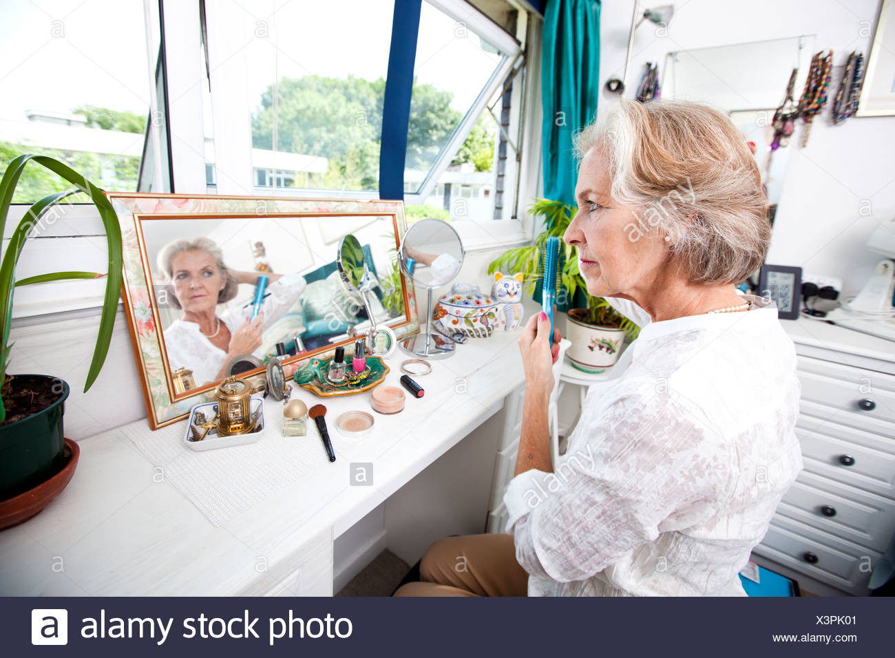 Senior woman combing her hair dresser house - Stock Image