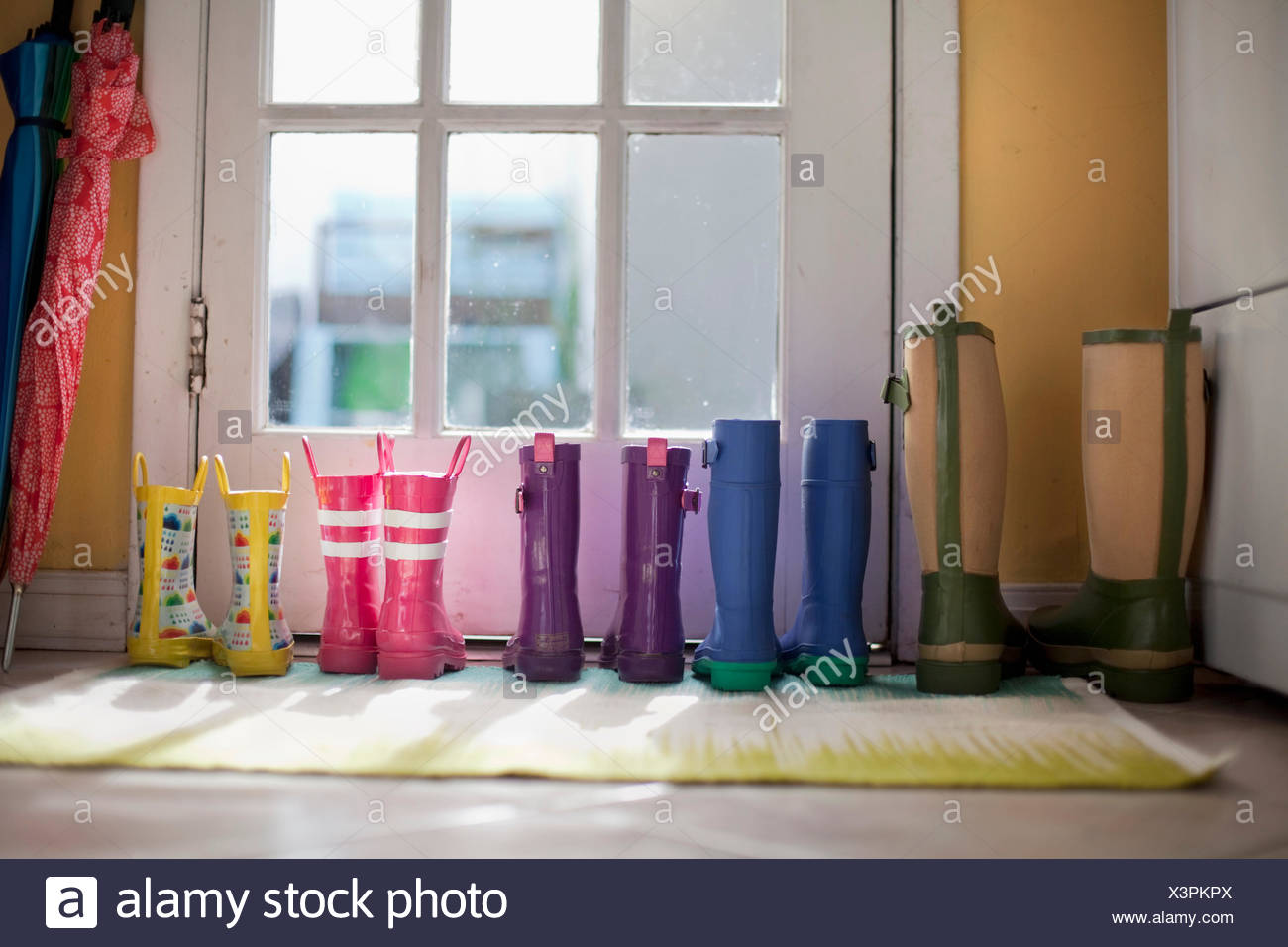 Tidy row of rubber boots at back door - Stock Image