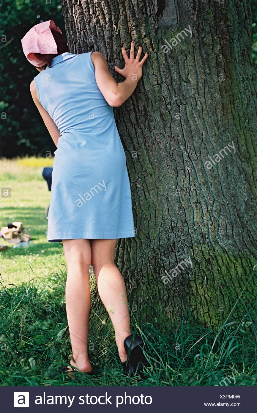 Woman, young, trunk, hide-and-seek, back view, park, game, fun, amusements, girls, young persons, teenagers, minidress, summer dress, dress, headscarf, tree, hide, observe, curiosity, summers, outside, very closely - Stock Image