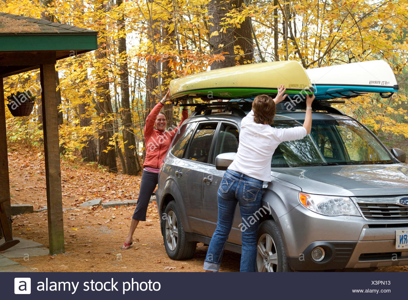 Two young women load kayaks on roof of vehicle at cottage near Oxtongue Lake, Muskoka, Ontario, Canada. - Stock Image