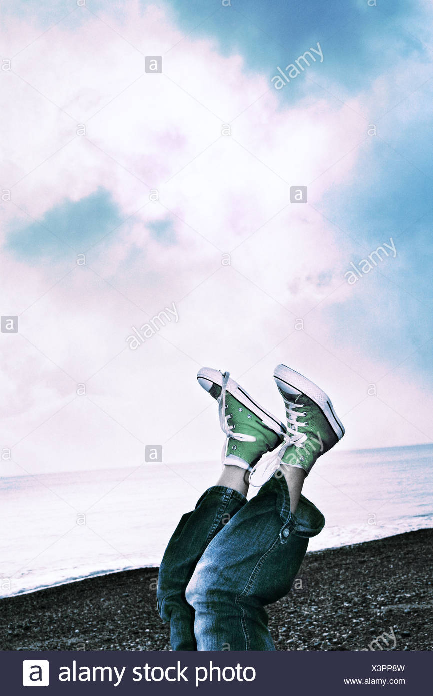 a young person lying on the beach with feet in the air - Stock Image