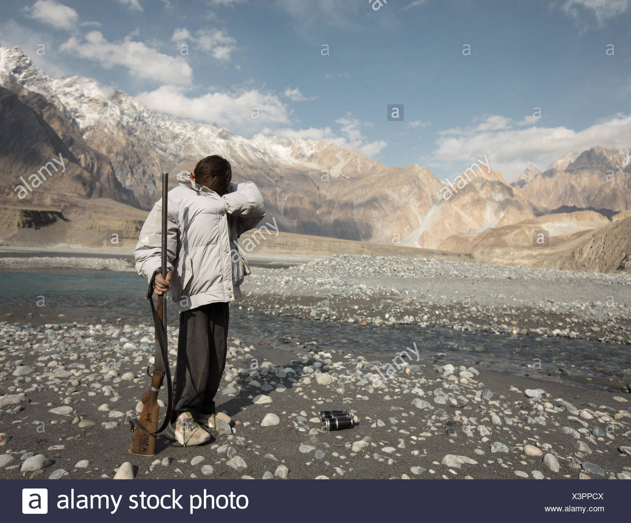 A duck hunter looks for a cartridge. - Stock Image