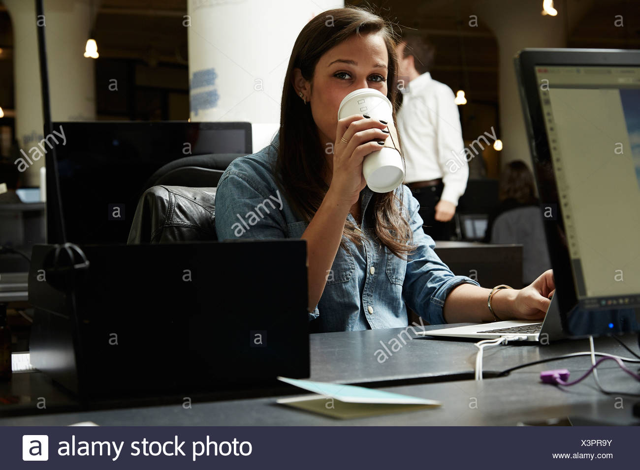Young woman drinking coffee in office - Stock Image
