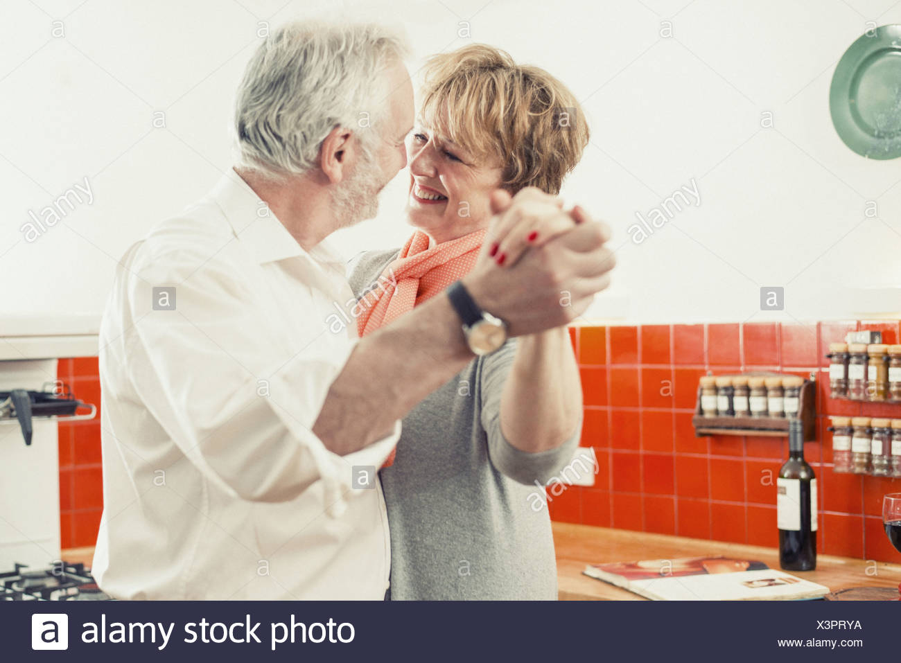 Couple dancing in kitchen - Stock Image