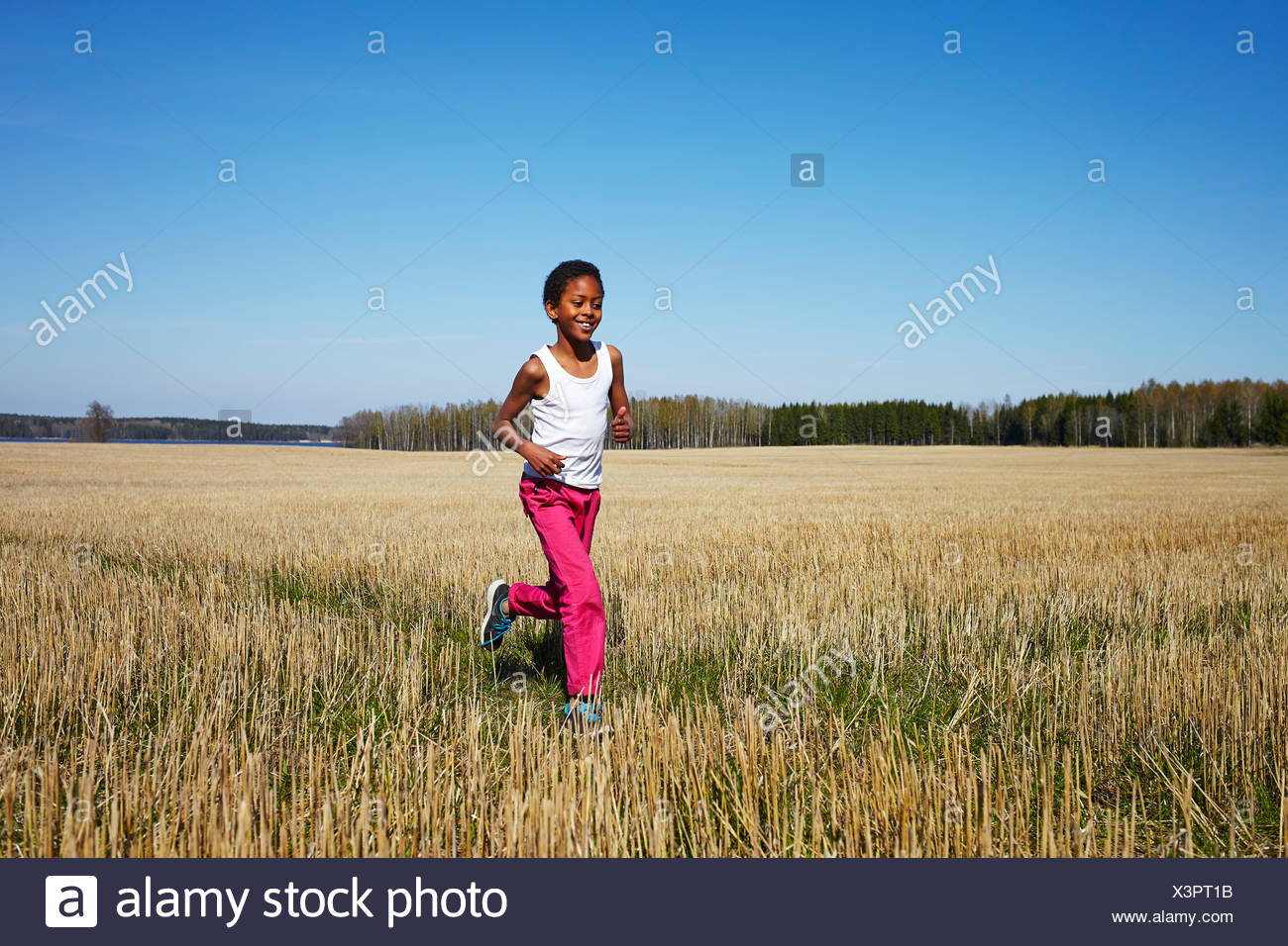 Sweden, Vastra Gotaland, Gullspang, Runnas, Boy (8-9) running in field Stock Photo