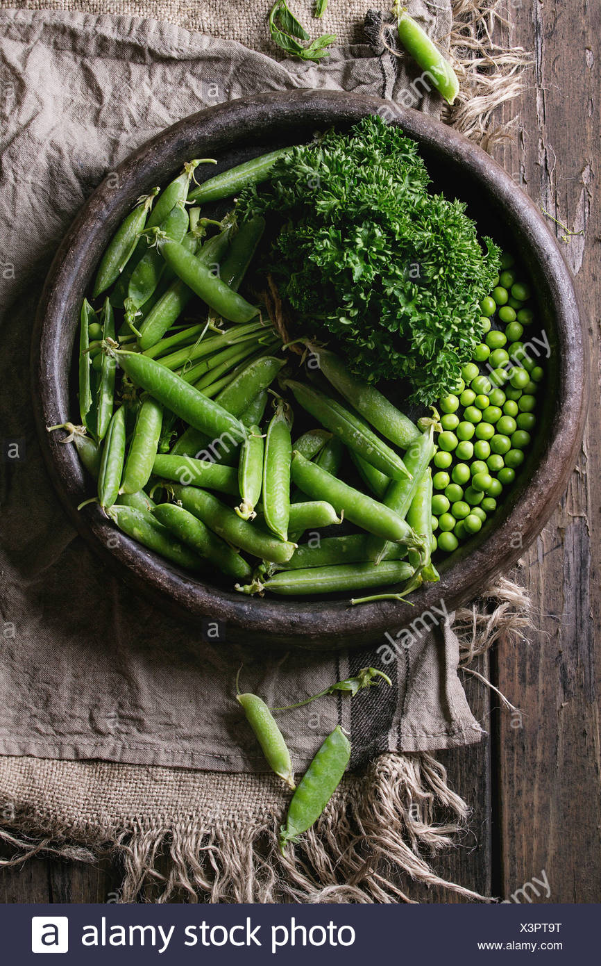 Young organic green pea pods and peas in terracotta tray and bundle of parsley over old dark wooden planks with sackcloth textile background. Top view - Stock Image